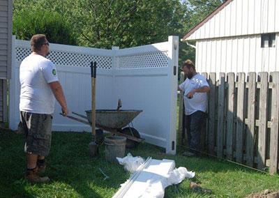 men installing white vinyl fence