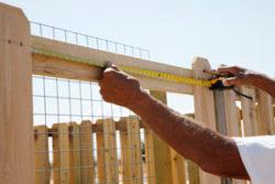 man measuring wood fence